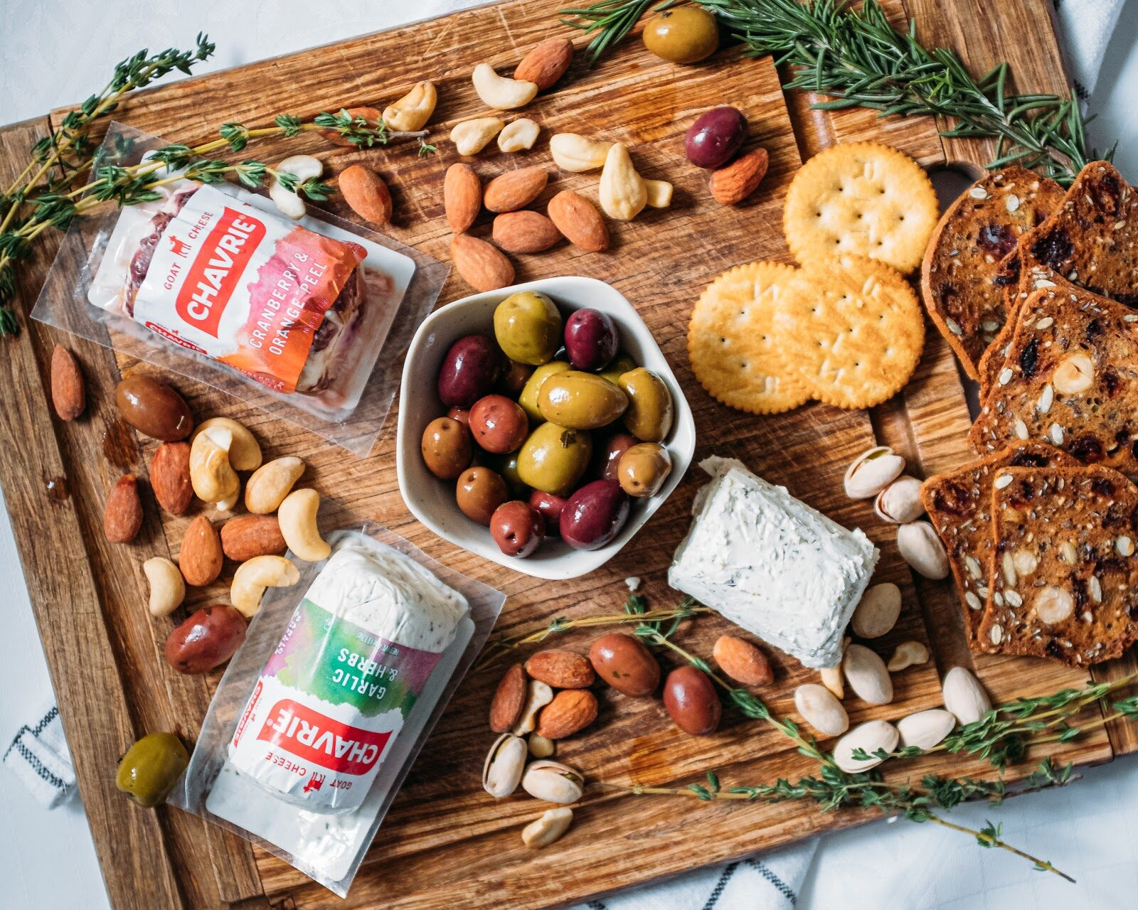 cheese board with chavrie garlic and herbs cranberry & orange peel, crackers, nuts, olives
