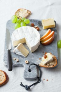cheese platter with ile de france camembert, apple slices and grapes