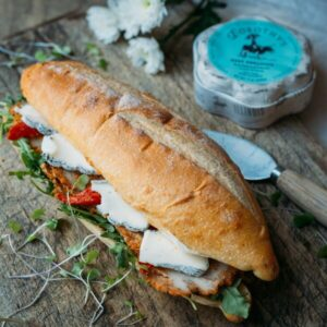 a baguette sandawich with turkey, tomato and dorothy's keep dreaming