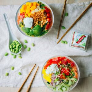 Colorful poke bowls with rice, vegetables, fruits et Chavrie goat cheese pyramid