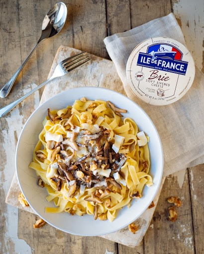 pasta dish with mushrooms, nuts and melted ile de france brie