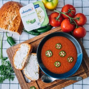 Bowl of gazpacho and Alouette smoky jalapeno spread on slices of bread