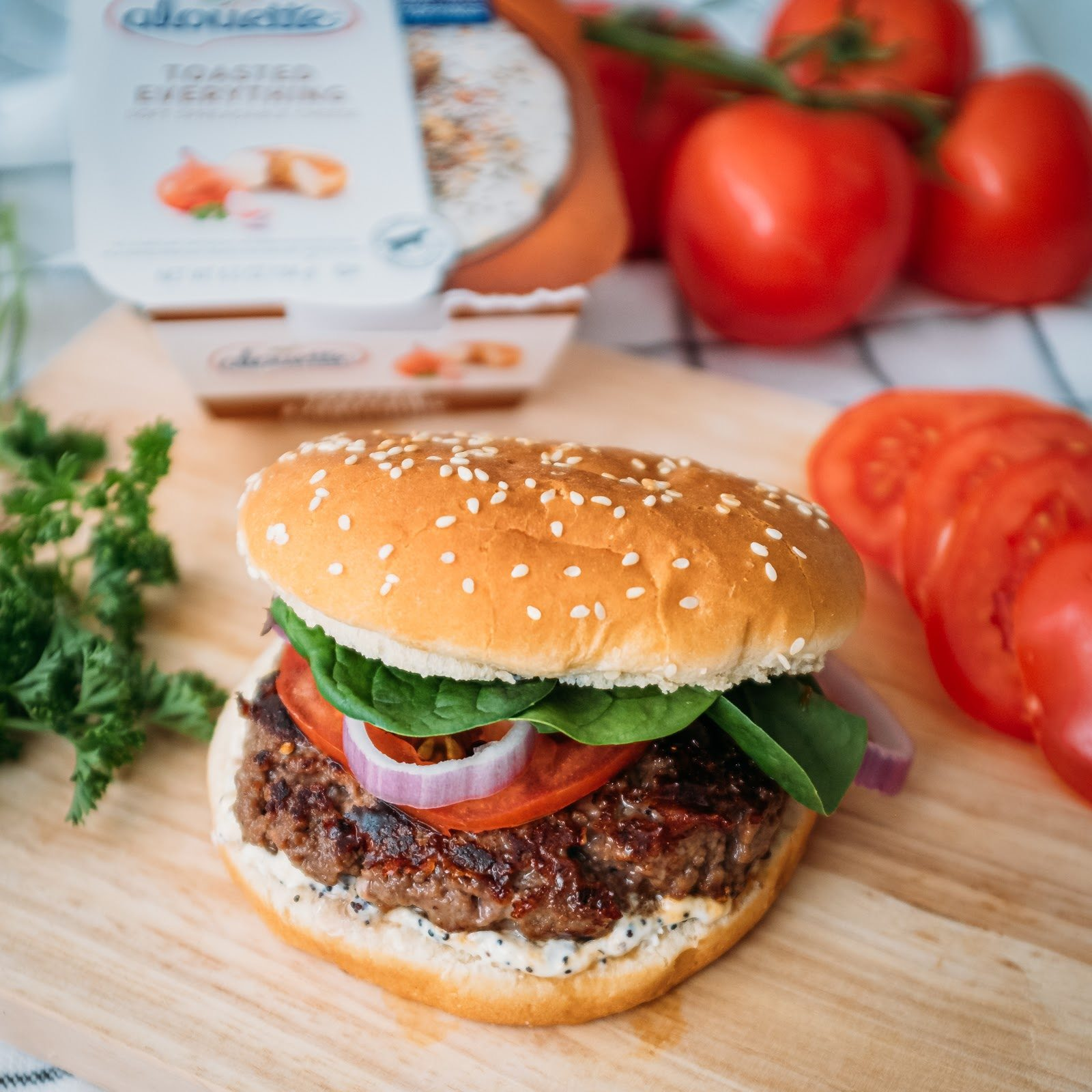 Hamburger with Aouette toasted everything, a patty, tomato, onion, salad