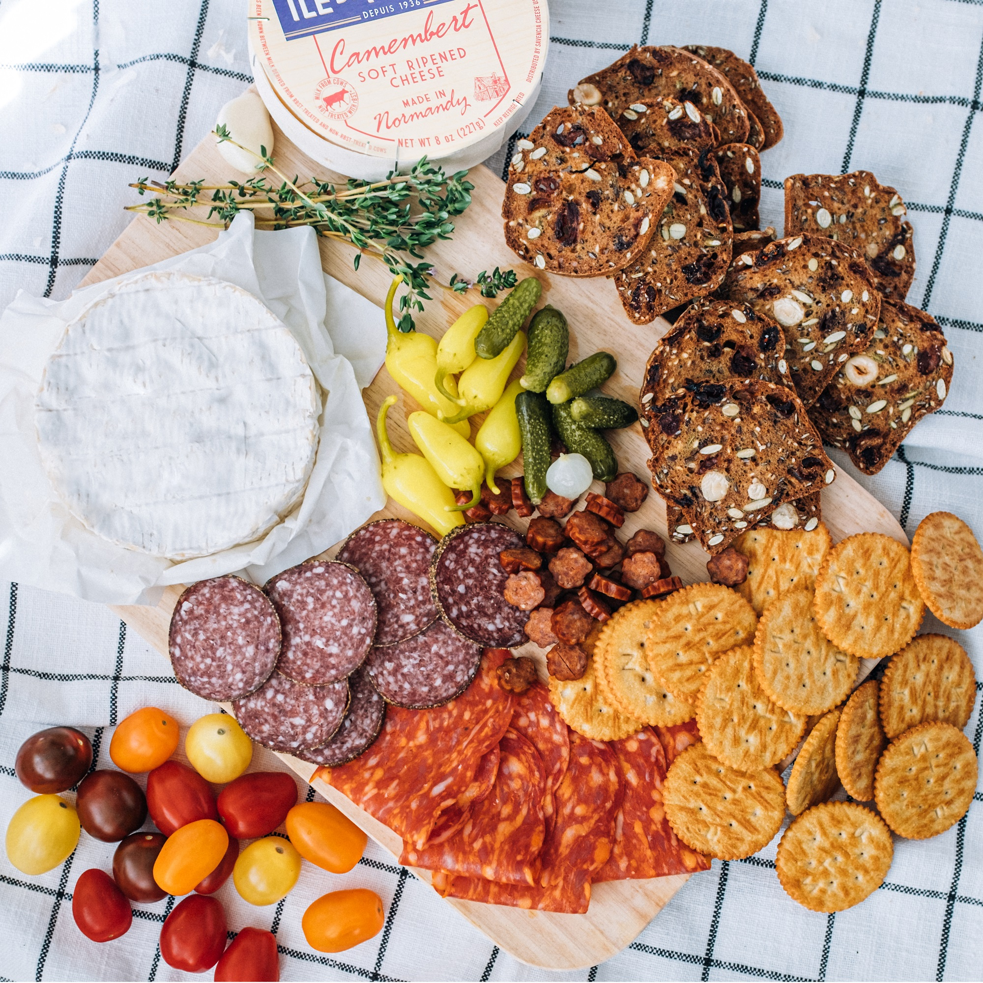 apero platter with ile de france camembert, charcuterie, vegetables and crackers