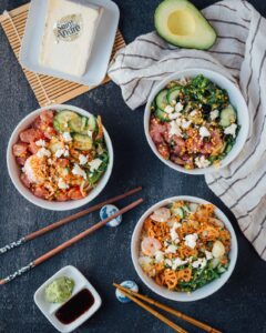 poke bowls with rice, salmon, shrimps, vegetables and saint andré cheese