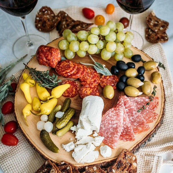 chavrie goat cheese log board with charcuterie, grapes, olives